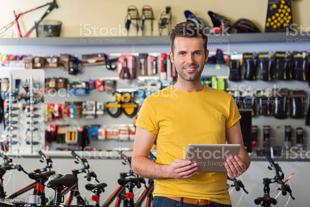 Sport store manager with digital tablet Portrait of manager of sports store, standing with digital tablet and smiling at camera. 30-34 Years Stock Photo