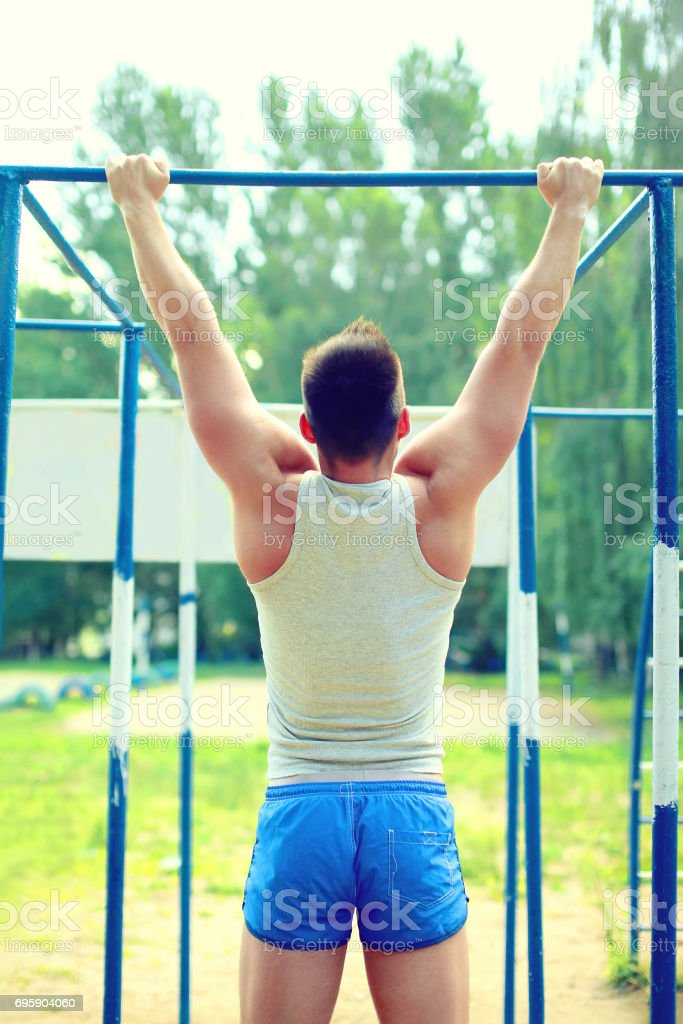 Sport, street workout concept - athlete doing pull ups on the...