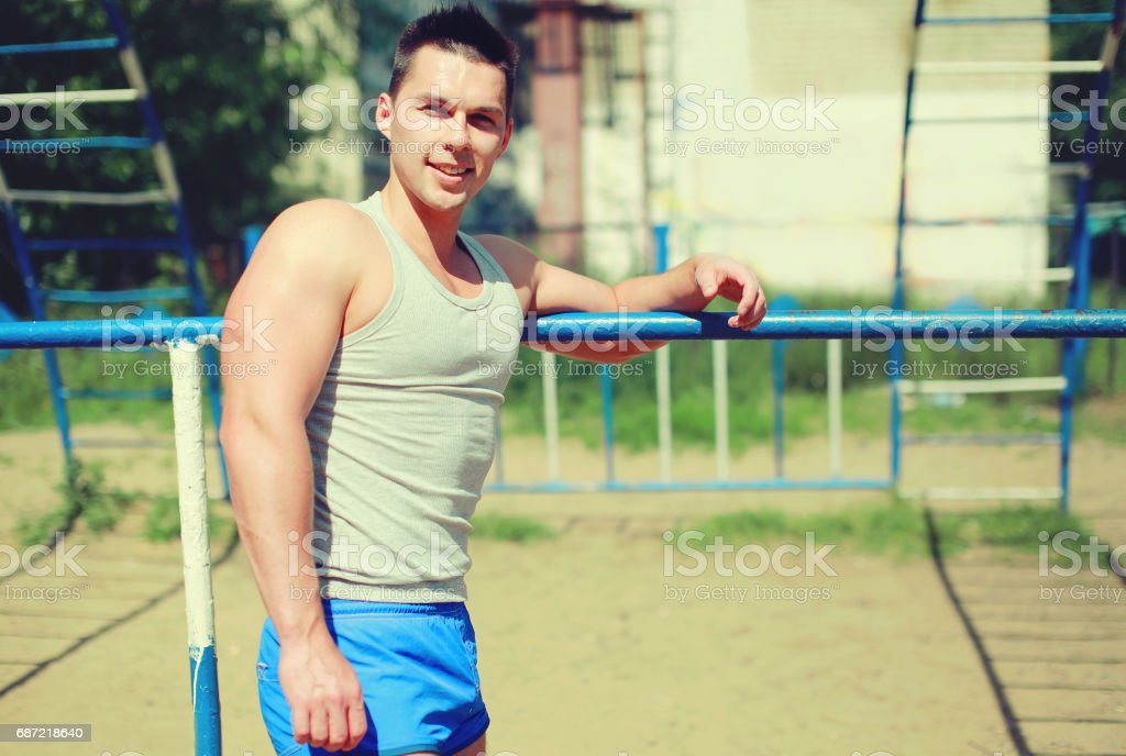 Sport, street workout concept - smiling sportsman near the horizontal...