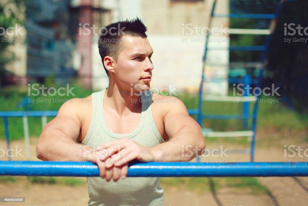 Sport, street workout concept - sportsman near the horizontal bar...