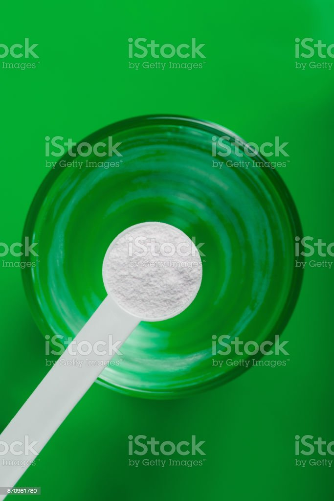 Sport supplement, creatine, hmb, bcaa, amino acid or vitamin - mesure with powder over a glass of water. Sport nutrition concept. stock photo