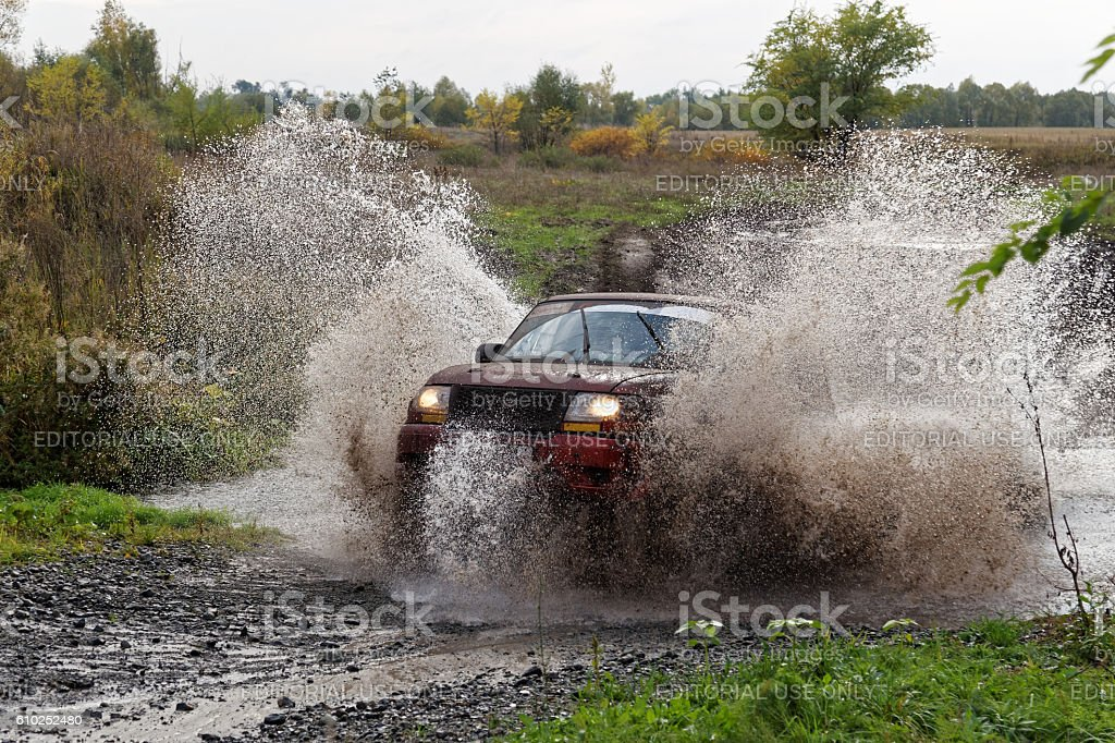 Sport SUV boosts water hurdle surrounded by splashes. – Foto