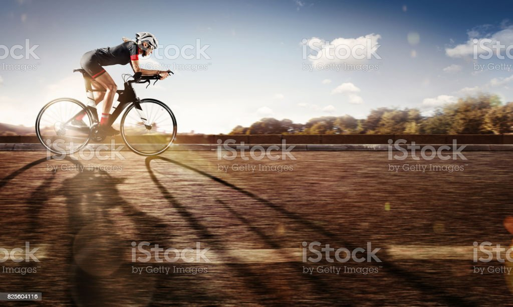Sport. The cyclist rides on his bike at sunset. Dramatic background. stock photo