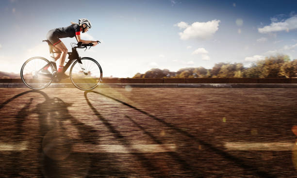 sport. the cyclist rides on his bike at sunset. dramatic background. - cycling stock pictures, royalty-free photos & images