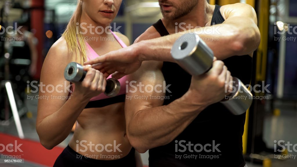 Sport trainer instructing young woman how to lift dumbbell properly,...
