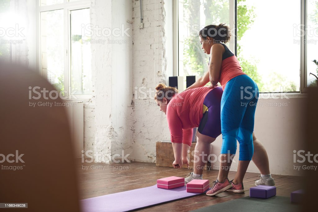Afro American lady helping Caucasian fat woman to work out correctly...