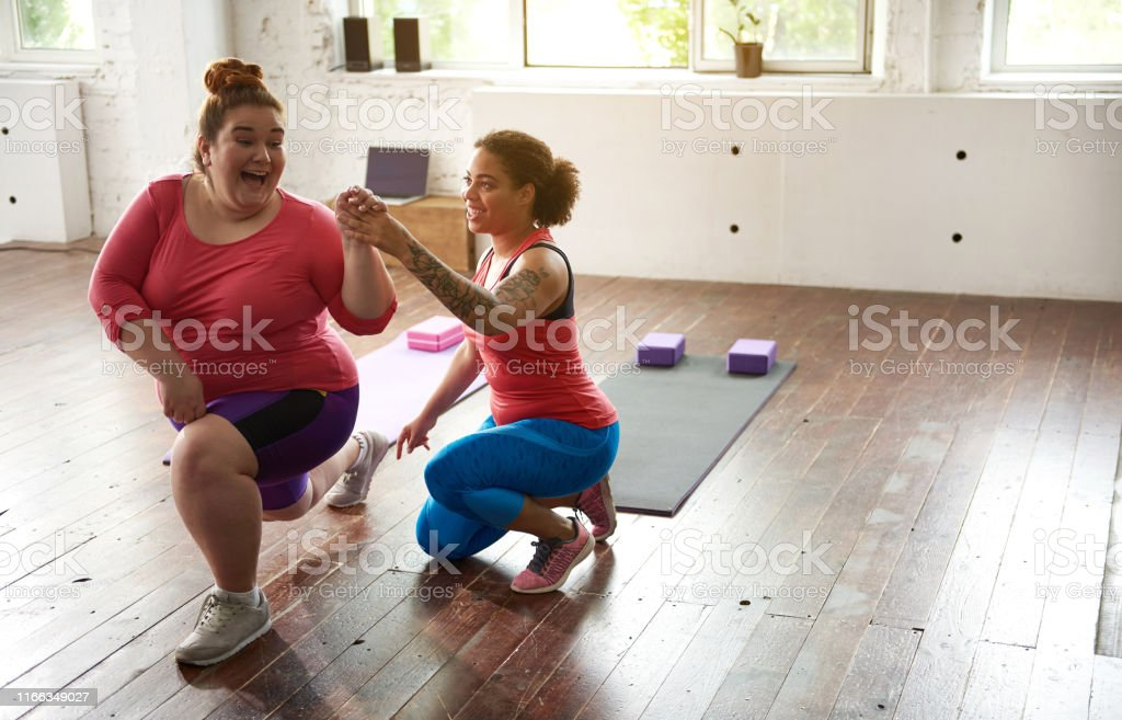 Afro American lady helping Caucasian woman to do lunges indoors and...