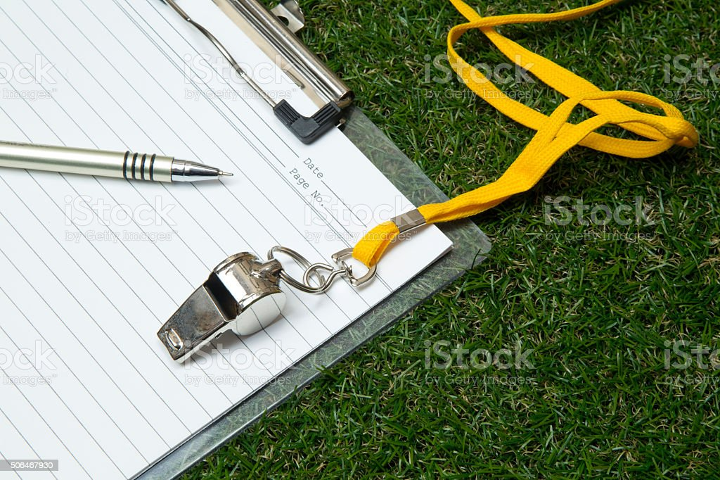 Sport whistle with pen and clipboard on grass Clipboard with metal sport whistle, pen and paper sheet on grass Agreement Stock Photo