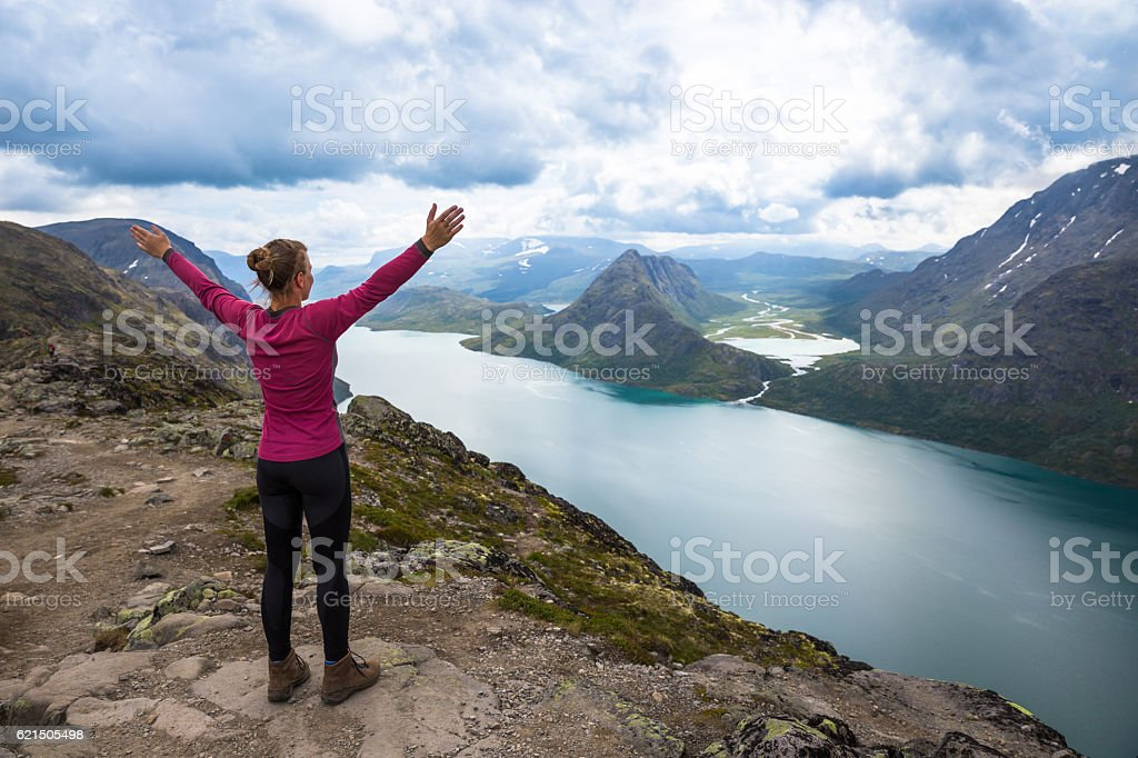 Sport woman hiking on Besseggen. Hikers enjoy beautiful lake and foto stock royalty-free
