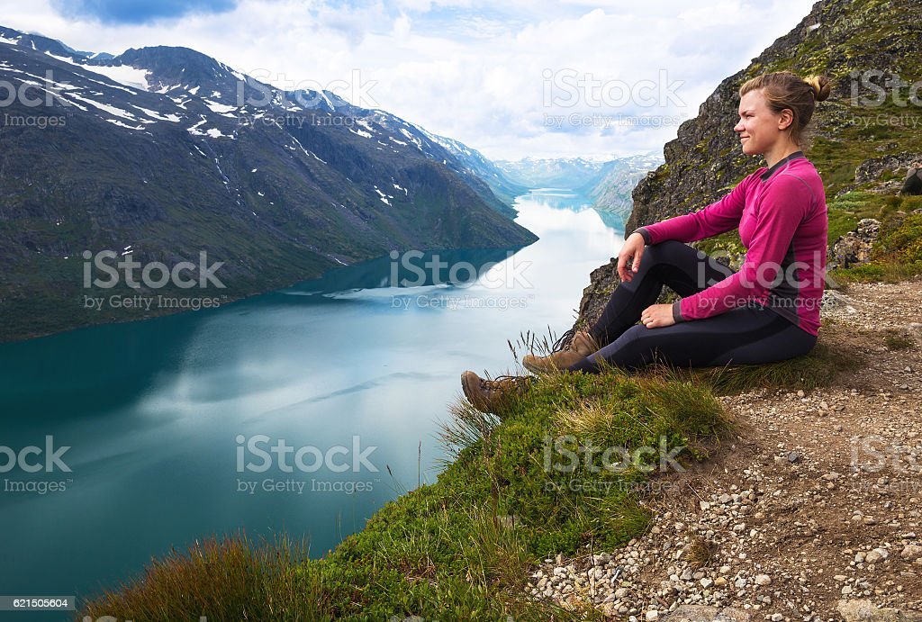 Sport woman hiking on Besseggen. Hikers enjoy beautiful lake and Lizenzfreies stock-foto