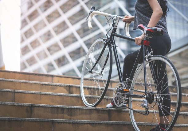 sportlerin ist ihr fahrrad die treppe hinauf tragen. - fahrradträger stock-fotos und bilder