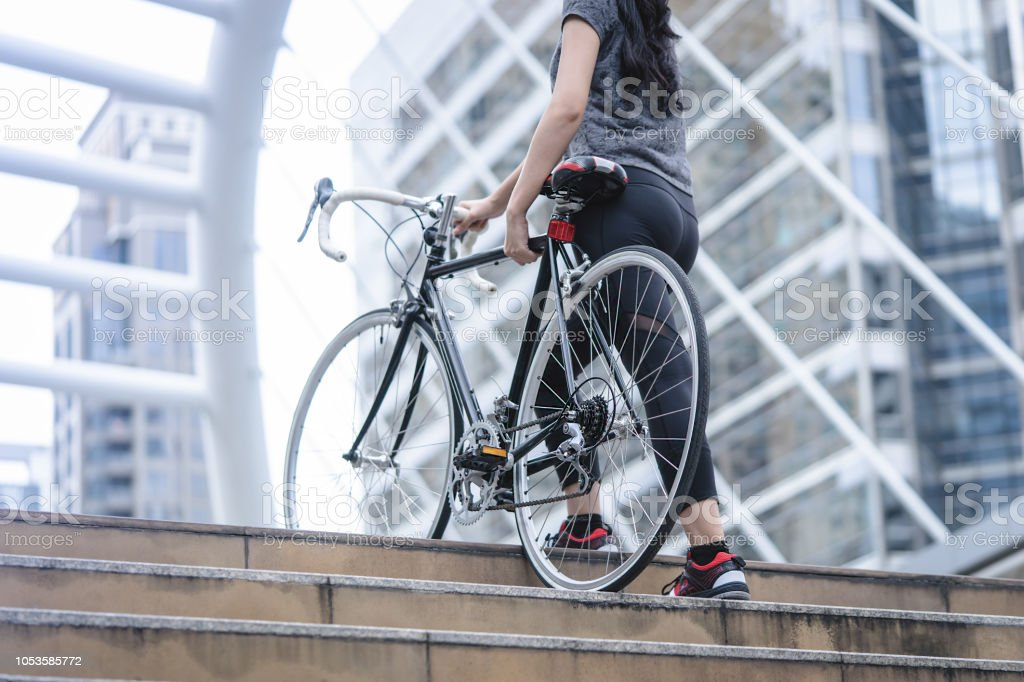 Sport woman is carrying her bike up the stair stock photo