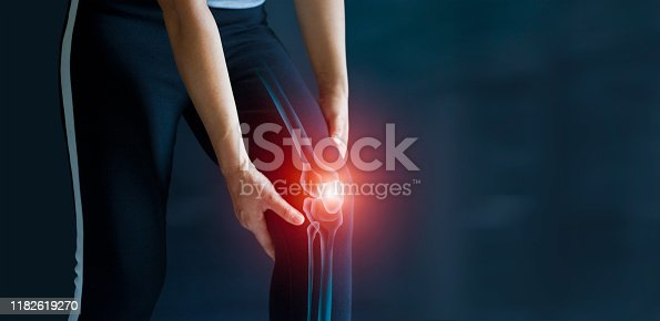 Sport woman suffering from pain in knee. Tendon problems and Joint inflammation on dark background. Healthcare and medical.