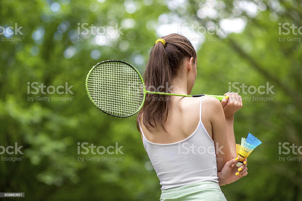 Sport woman with badminton racket and shuttlecock in the park stock photo