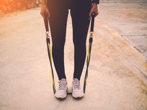 sport women doing outdoor exercise in the city with resistance band exercise