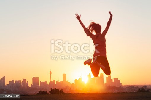 Sport women jumping and celebrating with arms raised. She is exercising at sunset or sunrise and is back lit. City of Sydney on the horizon in the background. Focus on background. She looks happy and has a sense of achievement.