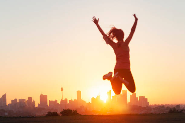 Sport women jumping and celebrating with arms raised. Sport women jumping and celebrating with arms raised. She is exercising at sunset or sunrise and is back lit. City of Sydney on the horizon in the background. Focus on background. She looks happy and has a sense of achievement. motivation stock pictures, royalty-free photos & images