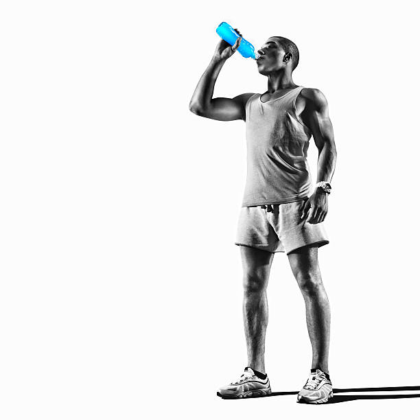 Sport. Young athlete drinking water of bottle after running stock photo
