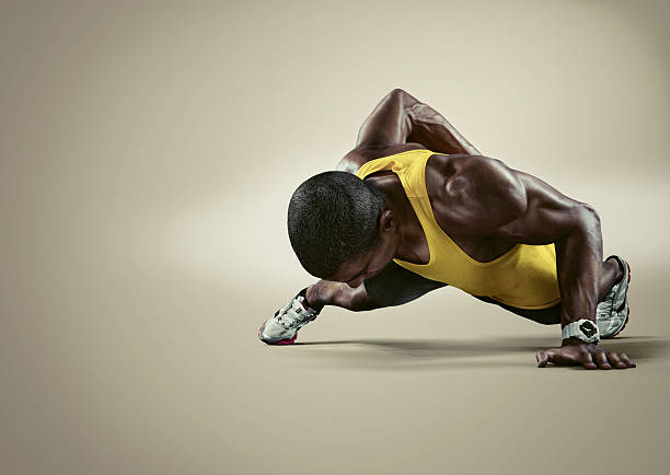 Sport. Young athletic man doing push-ups.