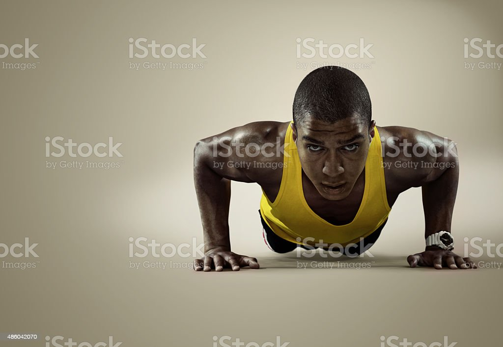 Sport. Young athletic man doing push-ups stock photo