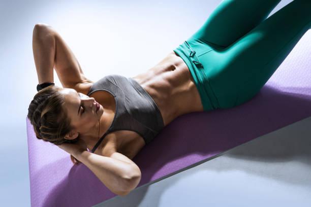 deporte. mujer joven y en forma haciendo ejercicio con músculos abdominales en un gimnasio. aislado. - músculo abdominal fotografías e imágenes de stock