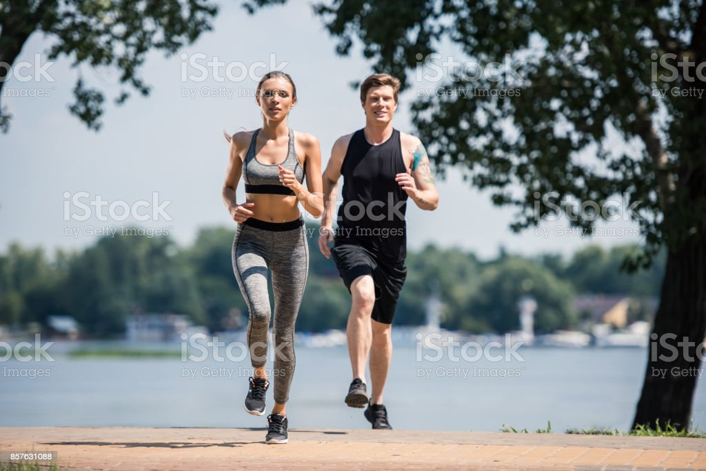 sportive couple jogging in park stock photo