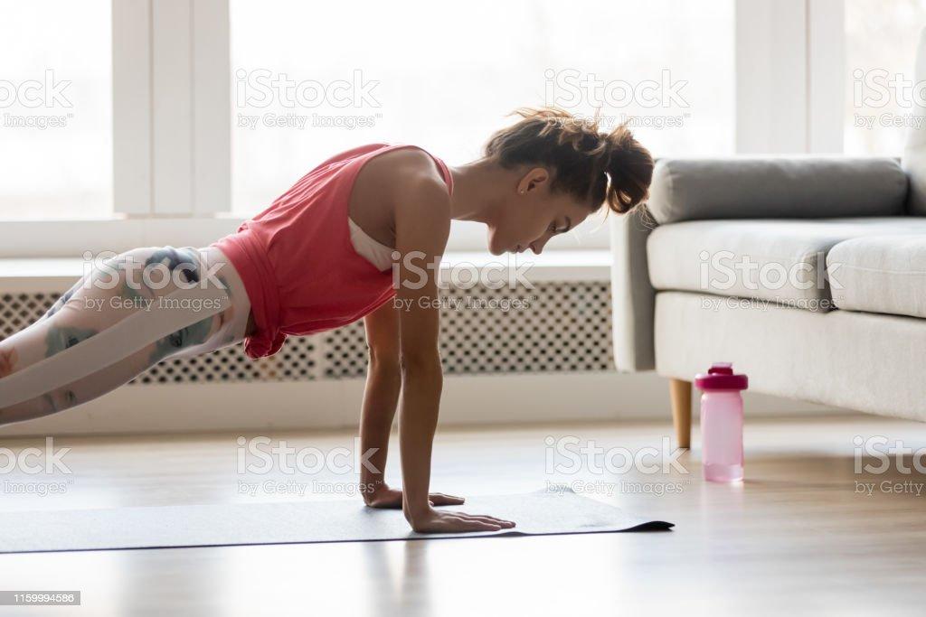 自宅でプッシュプレスアップ運動を行うスポーティな女の子 - 1人のロイヤリティフリーストックフォト