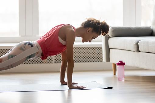 自宅でプッシュプレスアップ運動を行うスポーティな女の子 - 1人のストックフォトや画像を多数ご用意