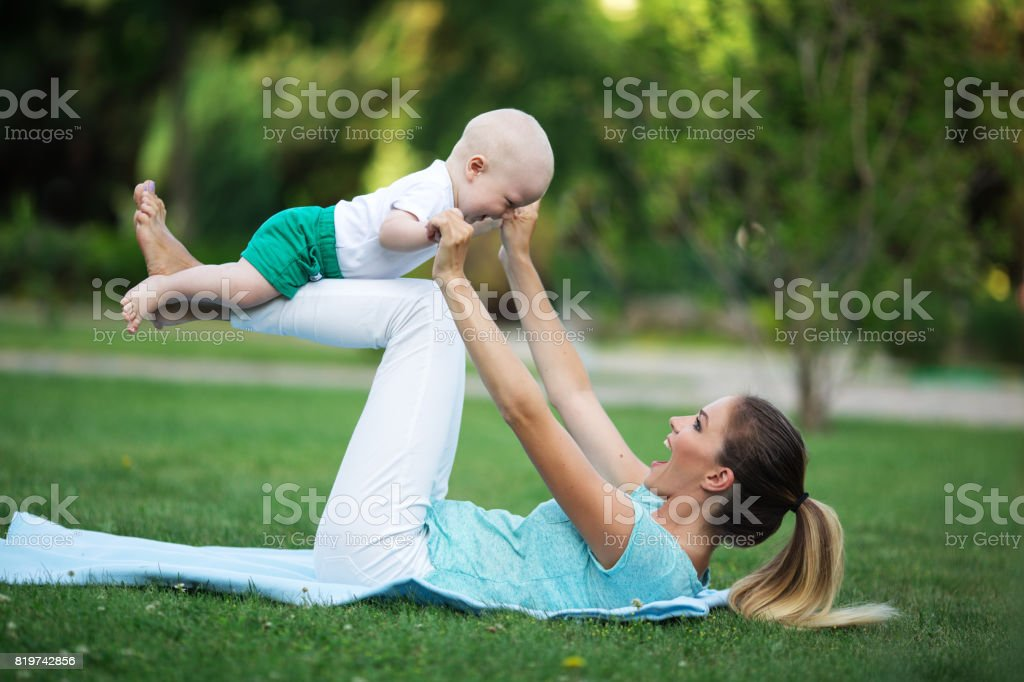 Sportive happy mother is doing workout on lawn with little son. Sports concept, summer time stock photo