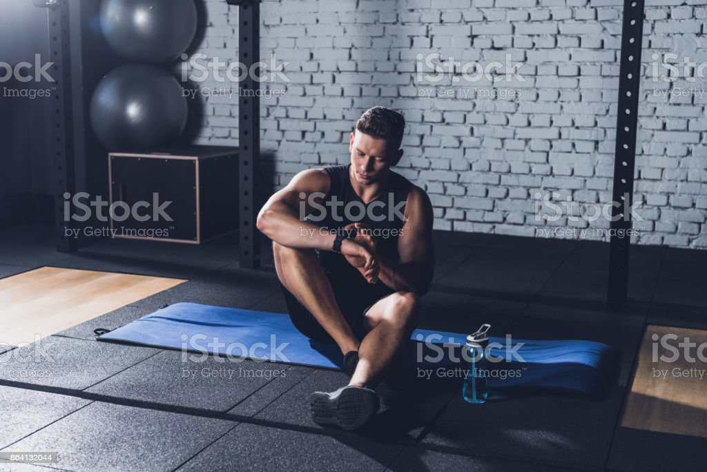 sportive man looking at smartwatch royalty-free stock photo