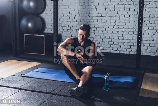 Sportive Man Looking At Smartwatch Stock Photo & More Pictures of Adults Only
