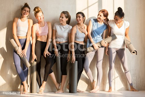istock Sportive multiracial girls talk laughing waiting for yoga class 1127548418