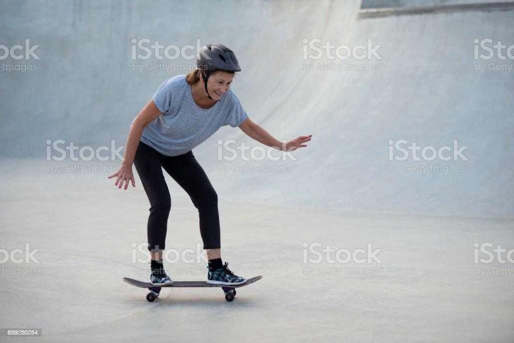 Mulher sênior esportiva praticando skate. - foto de acervo