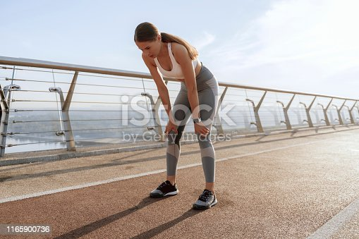 Health and sport practice. Young tired athletic woman in sport wear taking breath