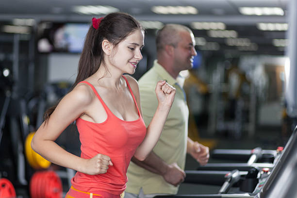 Sportive woman and man are jogging treadmill stock photo