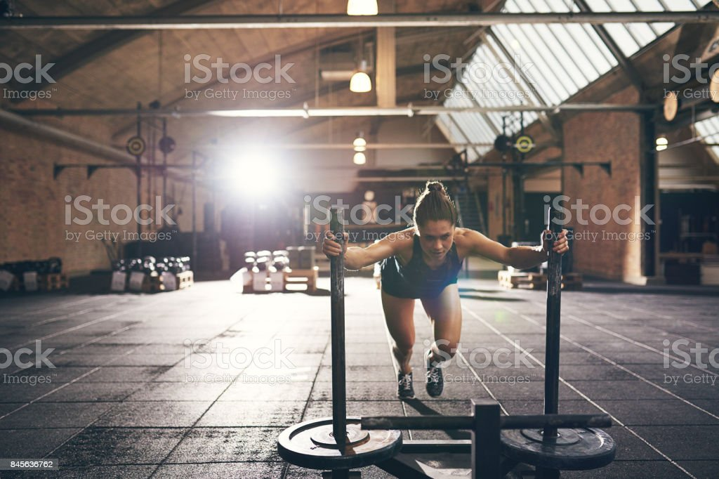 Sportive woman pushing bogie with weight disks stock photo