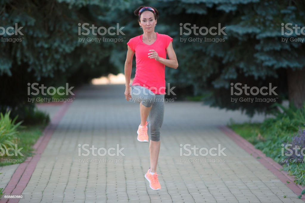 Sportive woman stretching before running. Sportive girl exercising outdoors. stock photo