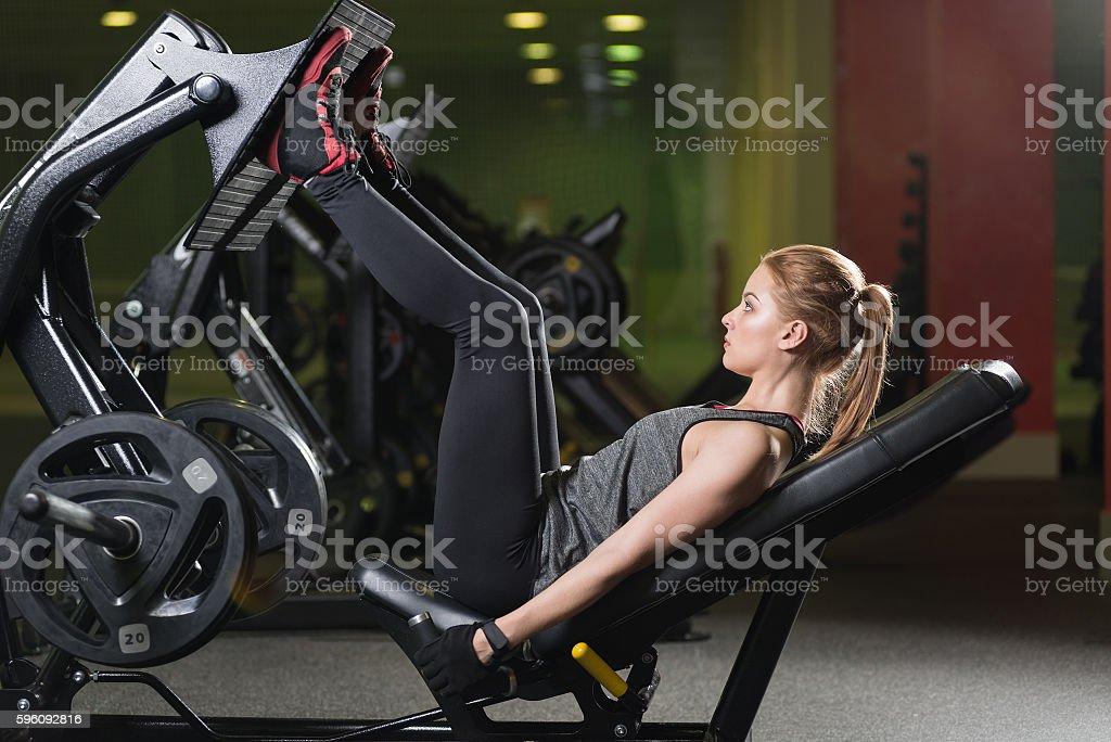 Sportliche Frau benutzt Hanteln Drücken Maschine für Beine. Fitnessraum. Lizenzfreies stock-foto