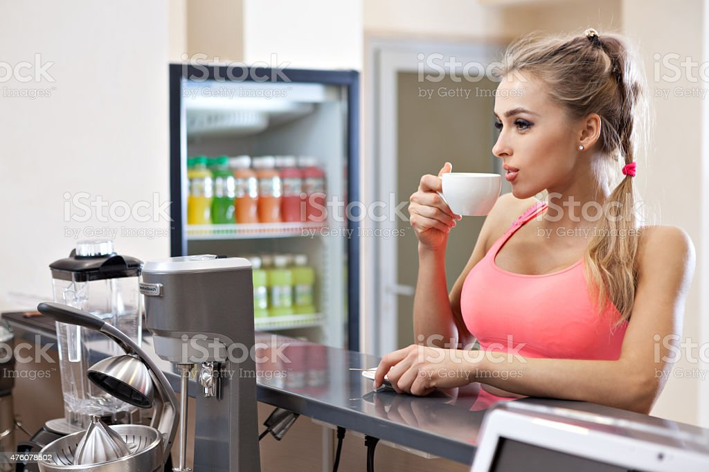 Sportive woman with cup in the gym bar stock photo