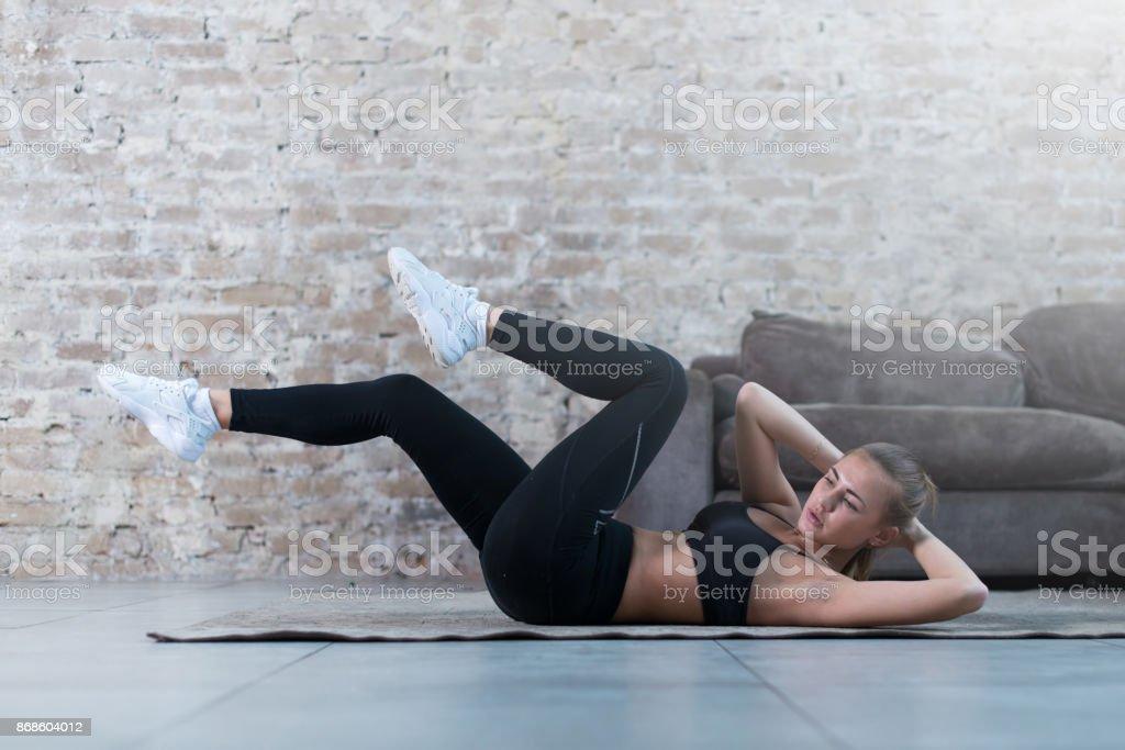Sportive jeune fille faire des exercices de crunch entrecroisé allongé sur un tapis au studio moderne - Photo