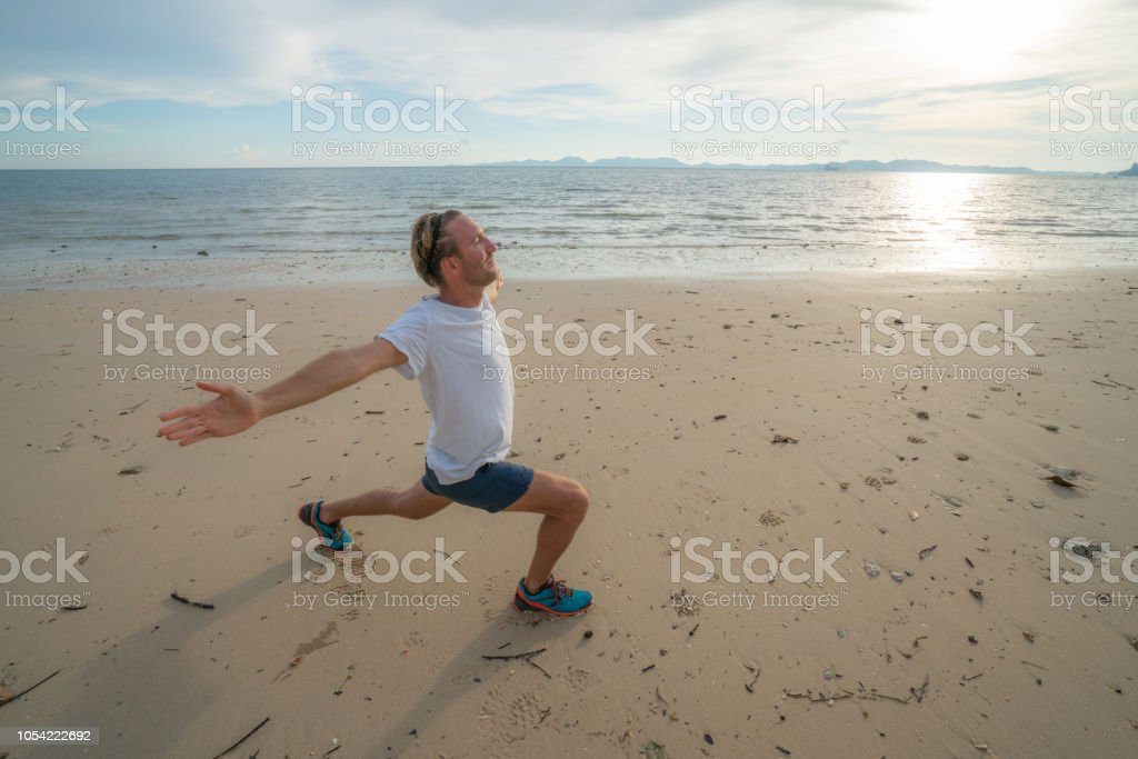 19d5c2b0aa0c Sportive young man stretching on beach after morning jogging royalty-free  stock photo