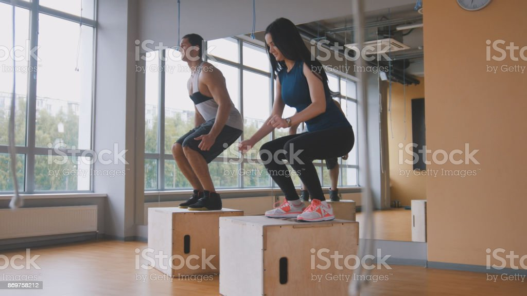 Sportive young woman and muscular man fitness instructor doing box jump exercise during a workout at the gym stock photo