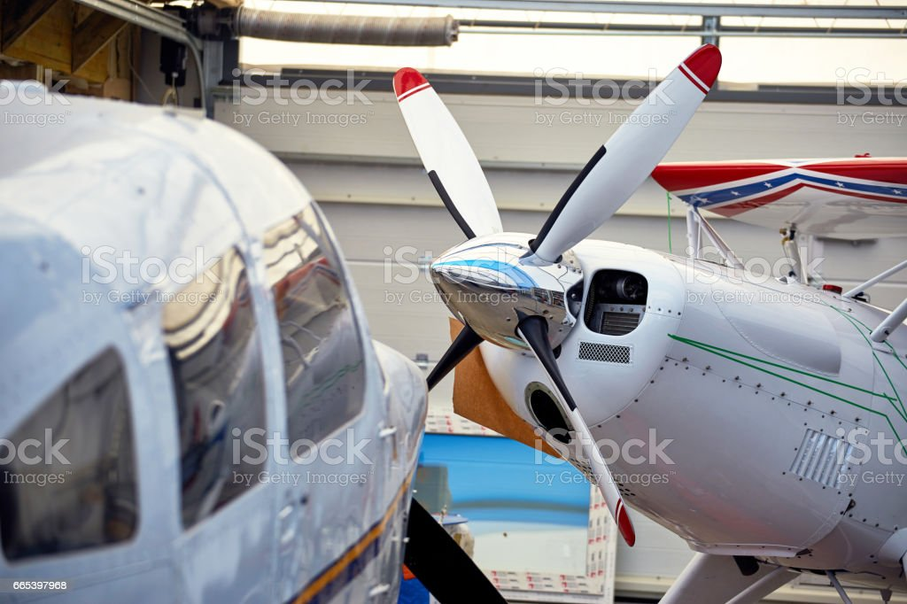 A sports aircraft in a hangar for service in the summer. stock photo