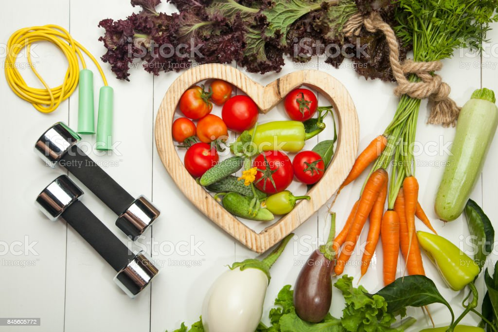 Sports and diet. Fresh vegetables, tomatoes, lettuce and carrot salad on a white wooden background stock photo