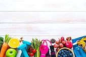 istock Sports and healthy food border: fruits, vegetables, nuts, dumbbels and tape measure. Copy space 1276373630