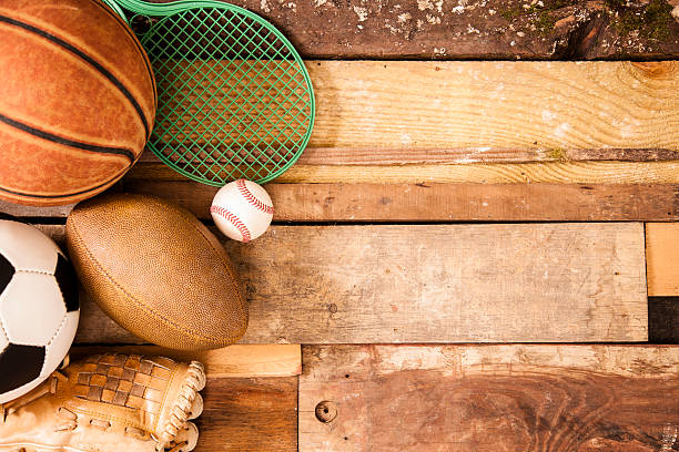 Sports Background: Equipment on unique wooden boards background. Sports concept. Basketball, tennis racket, baseball, glove, soccer ball, football to left of unique wooden boards background. Selective focus on wooden boards.  baseball sport stock pictures, royalty-free photos & images