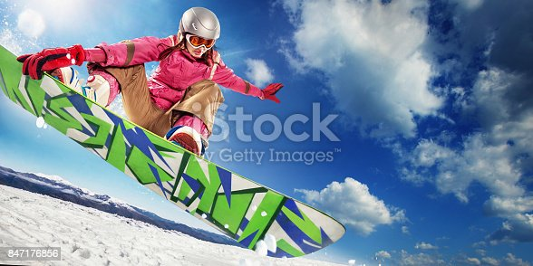 istock Sports background. Snowboarder jumping through air with deep blue sky in background. 847176856