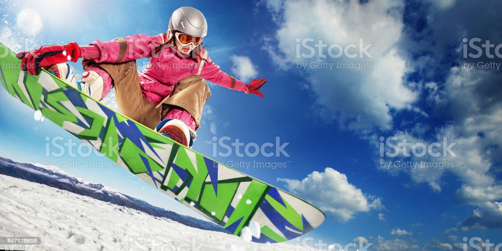 Sports background. Snowboarder jumping through air with deep blue sky in background. stock photo
