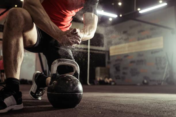 fondo deportivo. joven atleta preparándose para el entrenamiento crossfit. powerlifter mano en talco preparándose para hacer ejercicio con la kettlebell. - pesa rusa fotografías e imágenes de stock