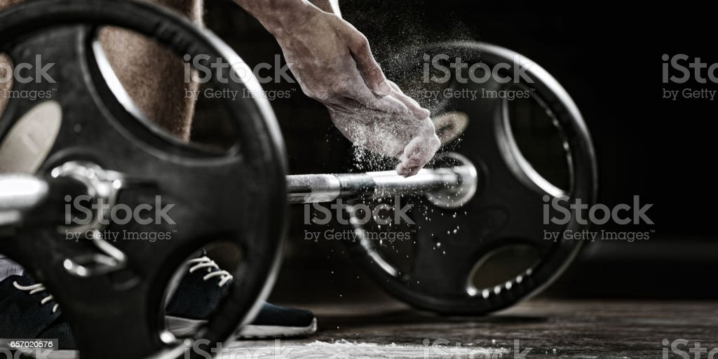 Sports background. Young athlete getting ready for weight lifting training. Powerlifter hand in talc preparing to bench press stock photo